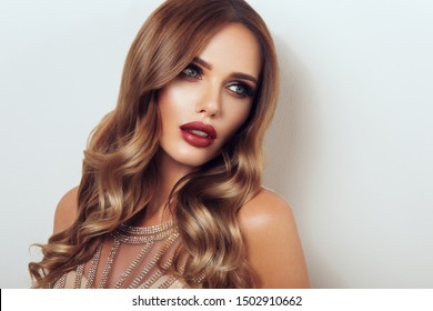 Girl with long and shiny wavy hair. Beautiful model with curly hairstyle .