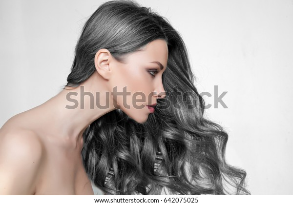 Girl long and shiny wavy hair . Beautiful model with curly hairstyle.  Beauty woman with luxurious long hair as background.  Beautiful woman with long smooth shiny  hair. Hairstyle. Hair cosmetics