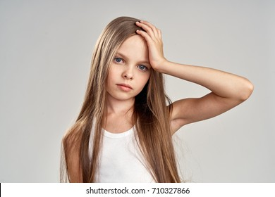 girl with long straight hair holding her head, portrait.
