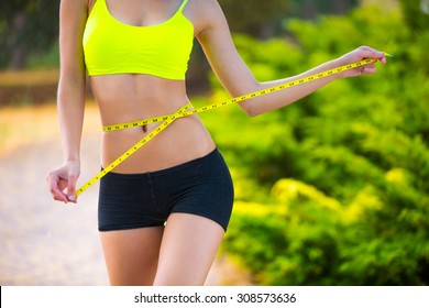 The girl was a long time on diet and sports. Now she is measuring her waist and she is pleased that have a good result.