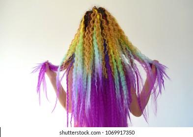 A girl with a long wavy hair painted in rainbow colors. Tunic hair kanikalon