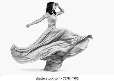 Girl in long yellow dress on isolated white background. A fashion model in the studio.