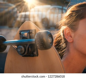 Girl with longboard on her shoulder and sun shining
