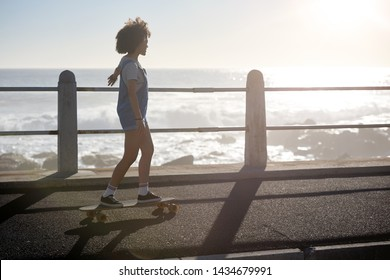 Girl longboarding riding skating enjoying sunshine and being by the ocean