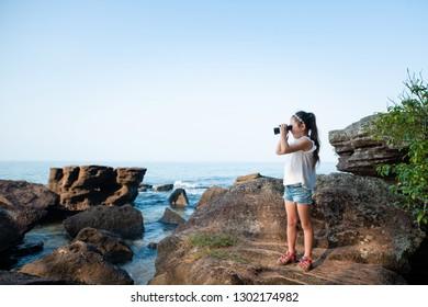 Girl look with binoculars in the sea
