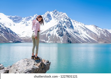 "Girl looking at the amazing mountain views of the turquoise waters from the ""Embalse del Yeso"" (Cast Lake) close to Santiago de Chile city in Andes mountains. Snow mountains and water reflections"