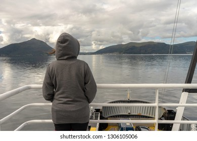 Girl looking at the beautiful scenery from a boat from Molde to Aalesund in Norway during summer holiday. Vacation, sunny, boat, girl, transport concept.