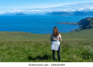 Girl looking at the beautiful scenery from the islands of Runde in Norway during summer holiday. Vacation, sunny, blue sky, girl, hiking concept.