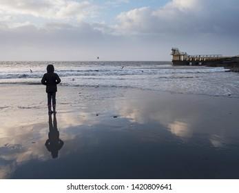 Girl looking at Blackrock diving tower. Salthill, Galway, Ireland. Dusk, calm ocean water. copy space.