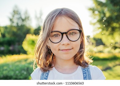 Girl looking at camera and smiling in nature. Summer leisure. Girl in glasses with black rim.