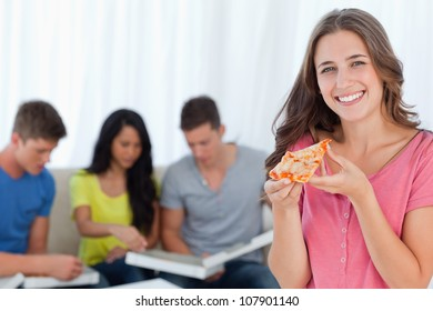 A girl looking at the camera smiling as she holds a slice of pizza in front of her friends