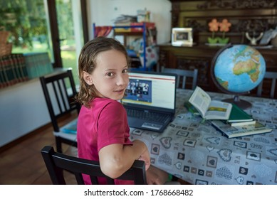 Girl looking at the camera studying infront of laptop