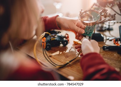 Girl looking circuit board throughout magnifying glass on the wooden table at home and building a robot as a school science project