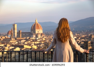 girl looking at the city of Florence from the viewpoint on the dawn