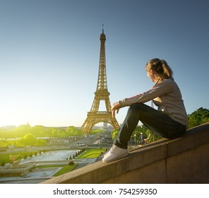 girl looking at the Eiffel tower in sunrise time, Paris, France