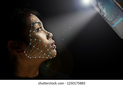 Girl looking up for facial recognition towards mobile phone in which her face has been digitized, with shart of light towards face on dark background, room for text.