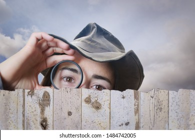 Girl with a looking glass peeking over a fence