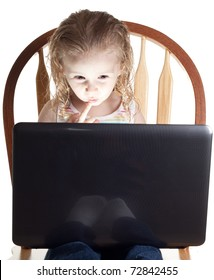 A girl looking at her computer with an inquisitive look on her face.  Something exciting and interesting is projecting from the screen.