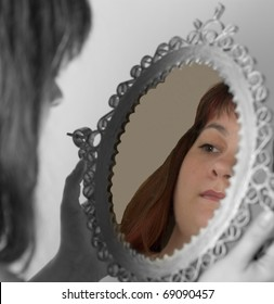 Girl looking at her face in the mirror