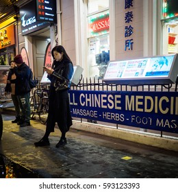 A girl looking at her smart phone in Chinatown. London, 2017