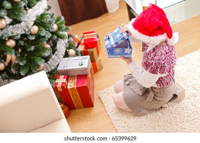 Girl looking inside an empty gift box in front of decorated christmas tree