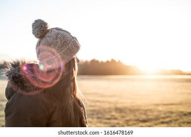 Girl looking into the sun on a cold winter morning