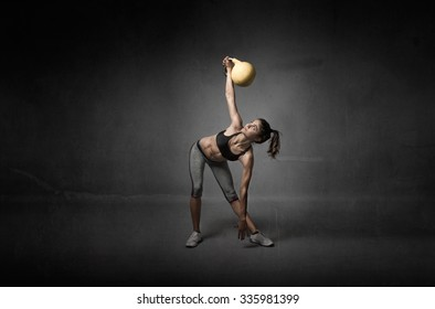 girl looking a kettlebell, textured background