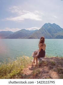 A girl looking at the lake from Riva di Solto on Lake Iseo with a beautiful view with nature and the mountains
