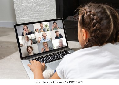 girl looking at laptop with videoconference children classmates standing on the table