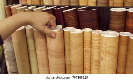Girl looking at linoleum flooring in interior store, close-up. Racks with linoleum rolls in wholesale warehouse.
