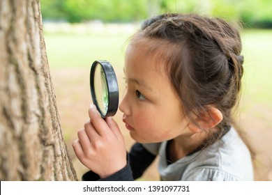 Girl looking with magnifying glass