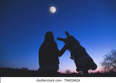 Girl looking at the Moon through a telescope. Elements of this image are my work.