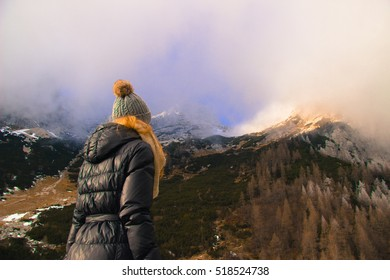 Girl looking at mountain peaks covered with snow on a sunny and foggy day