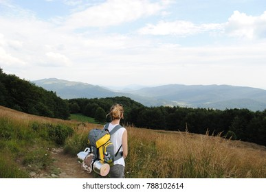 Girl looking at the mountains range located in the distance while hiking through different peak's trail. Backpack on shoulders with mat and hat. Summer holidays sport. Blonde hair. Recreation.