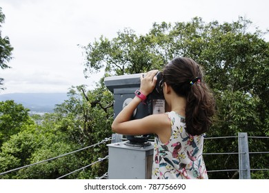 Girl looking at an Observatory Telescope at Joinville, a city on the south area of Brazil, at Santa Catarina State, in a cloudy day.