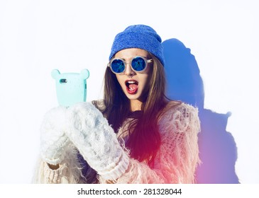 Girl looking on her phone. Bear funny case. Young beautiful woman winter portrait. Blue hat. Sunglasses. Hipster lifestyle. Happiness. Emotional face.
