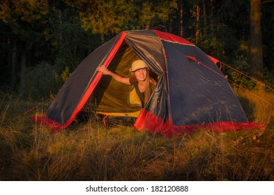 girl looking out from camp tent in forest