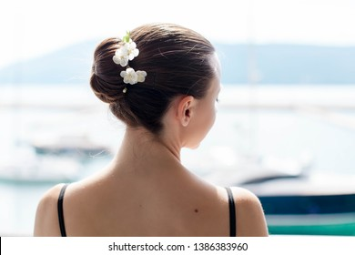 Girl is looking out open big window with view of sea and mountains. Ballerina stands back and has hair bun with spring flowers.