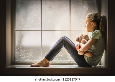 Girl looking out window holding teddy bear