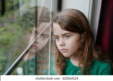 Girl looking out a window with a sad look on her face
