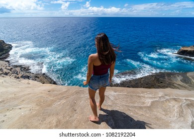 Girl looking over Spitting Cave in Oahu, HI
