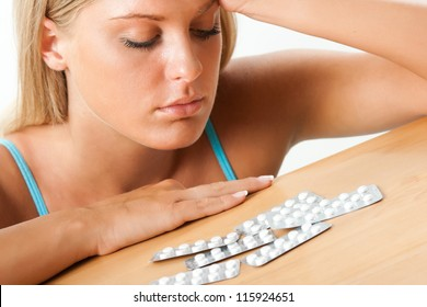 Girl looking at pills on the table, Taking pills
