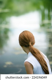 Girl looking at pond, rear view