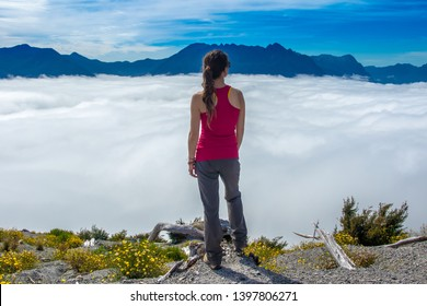 Girl looking at sea of clouds in the mountains