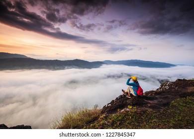 The girl are looking to  the  sea of mist on high mountain in Nakornchoom, Phitsanulok province, Thailand.