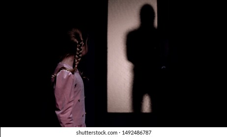 Girl looking at silhouette of criminal entering room, kidnapping concept, horror