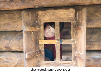 girl is looking to the small wooden window in a small log house at the public playground.