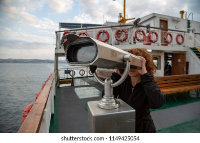 girl looking somewhere with ship binocular on ferry deck