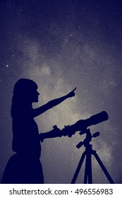 Girl looking at the stars with telescope beside her. My astronomy work.