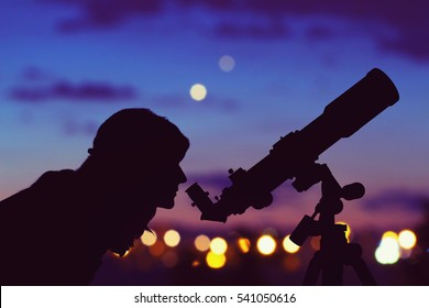 Girl looking at the stars with telescope beside her and de-focused city lights. My astronomy work.